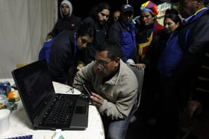 Chilean Miners Update: Volunteers watch a video of Chile's Mining Minister Golborne speaking