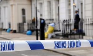 Police stand in front of a house where the body of an MI6 employee was found in London