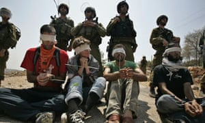 West Bank separation protesters sit in front of Israeli troops in Bil'in