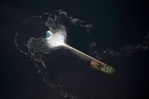 24 hours in pictures: Greenland: A ship melts an iceberg by spraying it with seawater