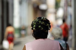 24 hours in pictures: Havana, Cuba: A woman wears hair curlers made from pipes and cables