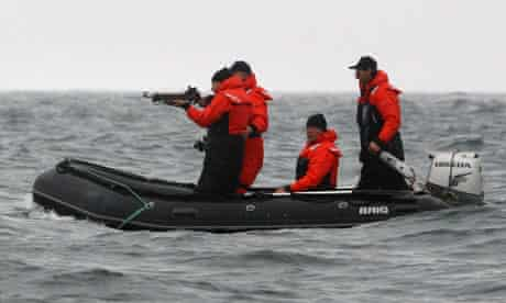 Russian prime minister Vladimir Putin aims at a gray whale in waters off the Kamchatka Peninsula