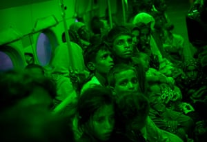 pakistan aftermath: Pakistanis sit in green glow of interior light in Afghan Army helicopter