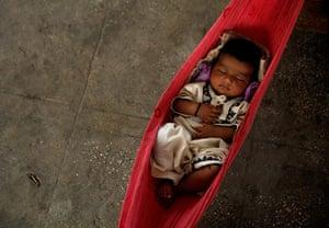 pakistan aftermath: Three-month-old Nasiba sleeps in a hammock while taking refuge in Sukkur