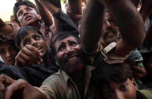 pakistan aftermath: Pakistanis fight with each other reach for milk during an aid distribution