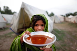 pakistan aftermath: A girl holds up her evening meal in Nowshera