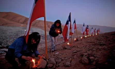Trapped Chilean miners-women plant flags, light candles