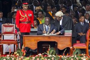 Kenya Constitution: Mwai Kibaki (C) signs the new constitution into law