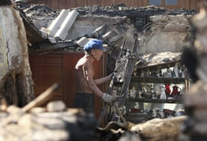 russian fire update: A Russian man walks through the remains of his burnt out home in Voronezh