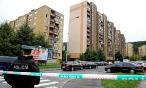 A police officer stands guard near the block of flats in Bratislava where a gunman killed six people
