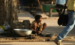 An Indian boy yawns as he washes plates