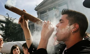 Participant in a Marijuana Party rally smokes a giant marijuana joint in downtown Vancouver