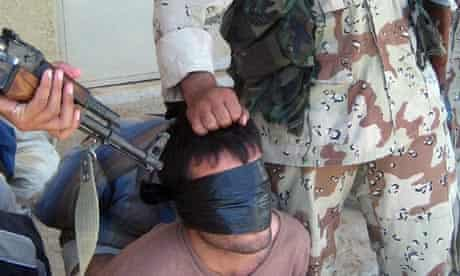 Iraqi soldiers guard a blindfolded detainee during an operation outside Baquba, north of Baghdad