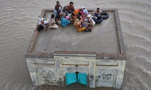 Family huddles on the roof of a mosque in the town of Sanawa, Punjab province