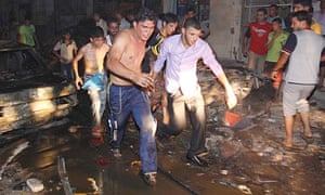Iraqis evacuate a victim of one of the explosions in Basra