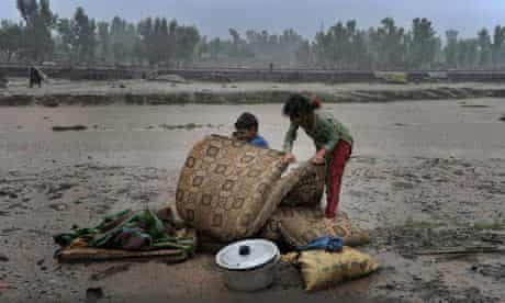 Children displaced by flooding in north-west Pakistan attempt to protect their belongings