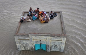 Pakistan aerial: A family takes refuge while awaiting rescue from flood waters