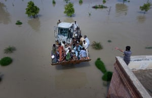 Pakistan aerial: A bulldozer carries flood victims to a near by rooftop in Muzaffargarh