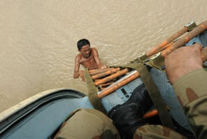 Pakistan aerial: A Pakistani flood survivor climbs onto an army rescue helicopter, Ghouspur