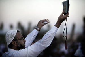 Eid begins: A Palestinian Muslim holds up a copy of the Qur'an