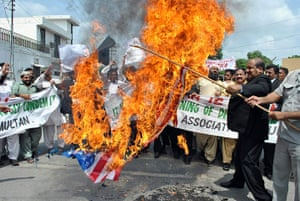 Qur'an Burning: Pakistani lawyers carry a burning US flag during a protest in Multan