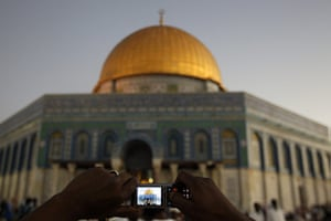 Eid begins: A Palestinian takes a photo of the Al-Aqsa Mosque before prayers
