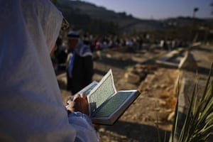 Eid begins: A Palestinian Muslim woman reads verses of the Qur'an over the grave