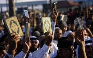 Eid festival: Palestinian Muslims hold up copies of the Qu'ran during Eid al-Fitr prayers