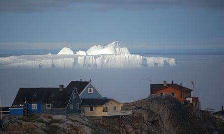 An ice shelf looms over houses in Nuuk, the capital of Greenland.