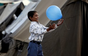 Six weeks later: Pakistan: Flood victim, wearing new clothes donated by a charity,plays with a balloon