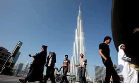 A group of Emiratis walk past the Burj Dubai Tower