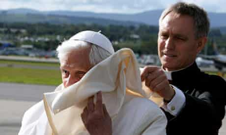 Papal secretary Georg Gänswein helps Pope Benedict as he arrives for his UK visit