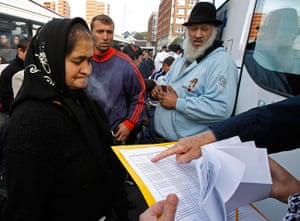 Roma Return : Immgration officer checks list as Roma families wait to board a bus