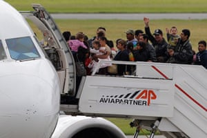 Roma Return : Roma families wave before boarding a flight to Romania