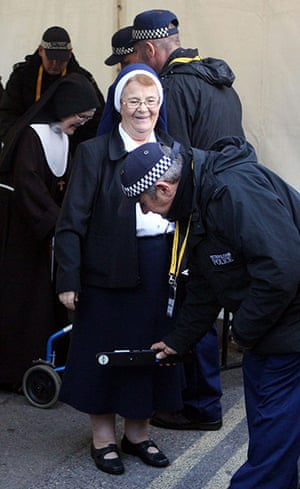 Pope Day 2: A nun is checked by police as she passes through a security checkpoint