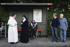 Pope Day 2: A nun stands with a clergy man at a bus stop