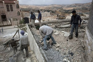 Middle East Peace Talks: Palestinian laborers work at a new neighborhood in the West Bank