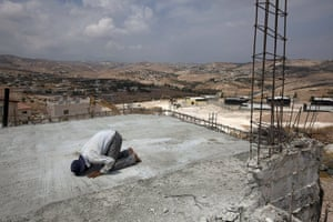 Middle East Peace Talks: A Palestinian laborer prays as he takes a break from work in the West Bank