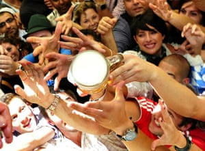 Oktoberfest in Munich: Revellers reach out to get a one-litre mug of beer in the Hofbrauhaus tent