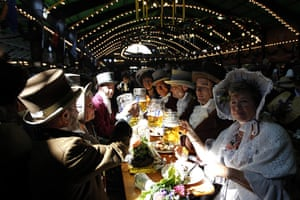 Oktoberfest in Munich: Visitors wearing historical dress drink beer and eat during the second day