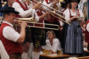 Oktoberfest in Munich: A woman sits as musicians play during the second day