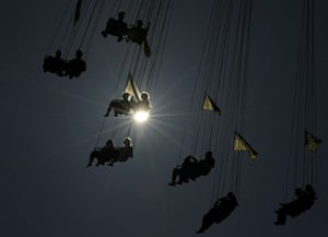 Oktoberfest in Munich: Visitors of the Oktoberfest beer festival sit in a chairoplane at the fair