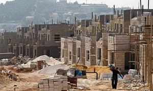 A labourer walks through a construction site in West Bank settlement of Elazar