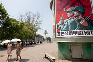 North Korea: Pyongyang street with one of North Korea's ubiquitous propaganda posters