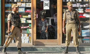 Indian policemen stand guard as Kashmiri people shop during a relaxation of curfew in Srinagar