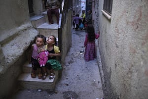 Muhammed Muheisen: Palestinian girls play with a doll while sitting in front of a house
