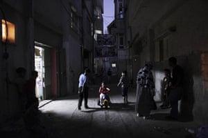 Muhammed Muheisen: Palestinians gather in an alley of Al-Amari refugee