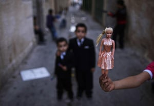 Muhammed Muheisen: A Palestinian girl shows her toy while playing in an alley