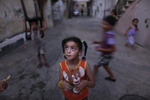 Muhammed Muheisen: A Palestinian girl holds her toy as she hears her mother calling her
