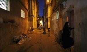 Muhammed Muheisen: A Palestinian woman talks with her neighbor as children play